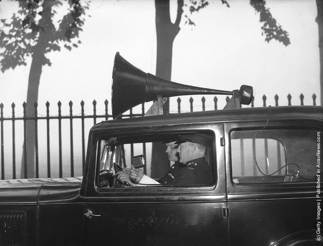 1936: Two police officers patrol the misty streets of London in a new loudspeaker van, providing tips on road safety to drivers and pedestrians