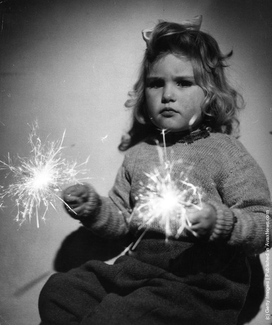 1952: A little girl playing with sparklers on Guy Fawkes Night or Bonfire Night