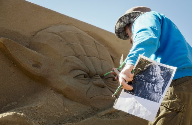 """A sculptor works on his creation during the Sand Sculpture Festival """"Sand Fantasy"""" in Almaty, Kazakhstan, April 15, 2016. (Photo by Shamil Zhumatov/Reuters)"""