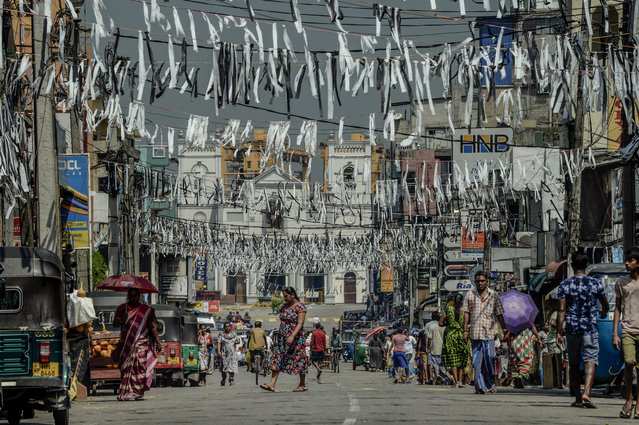 Locals pass funeral ribbons hung across the road leading to St Anthony's Church on April 24, 2019 in Colombo, Sri Lanka. At least 321 people were killed and 500 people injured after coordinated attacks on churches and hotels on Easter Sunday in and around Colombo as well as at Batticaloa in Sri Lanka. According to reports, the Islamic State group have claimed responsibility on Tuesday for the attacks while investigations show the attacks were carried out in retaliation for the Christchurch mosque shootings last month. Police have detained 40 suspects so far in connection with the suicide bombs while the government blame the attacks on local Islamist group National Thowheed Jamath (NTJ). (Photo by Atul Loke/Getty Images)