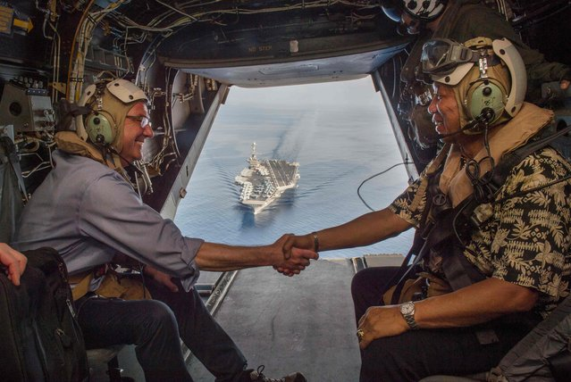 In this image released by the US Department of Defense, US Secretary of Defense Ash Carter (L) and Philippine Secretary of National Defense Voltaire Gazmin shake hands on a Marine Corps V-22 Osprey as they depart the USS Stennis after touring the aircraft carrier as it sails the South China Sea April 15, 2016. (Photo by Senior Master Sgt. Adrian Cadiz/AFP Photo)