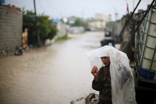 A Palestinian boy cover his head with a plastic sheet on a rainy day in Khan Younis in the southern Gaza Strip February 22, 2016. (Photo by Ibraheem Abu Mustafa/Reuters)