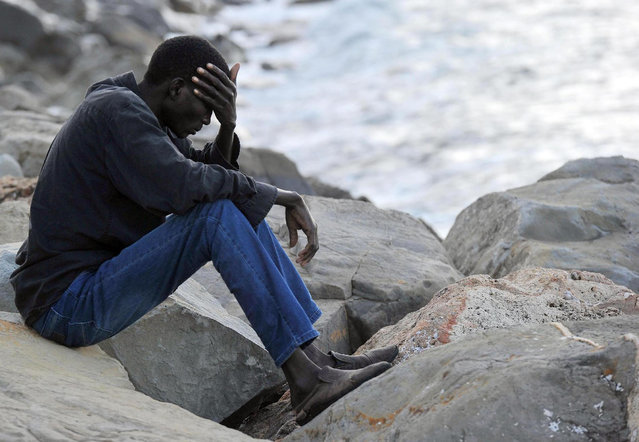 A migrant sits on rocks by the sea in Ventimiglia, at the Italian-French border, Tuesday, June 16, 2015. Police at Italy's Mediterranean border with France on Tuesday forcibly removed a few dozen African migrants who have been camping out for days in hopes of continuing their journeys north. It was a violent scene Italy is using to show that Europe needs to do more to deal with the crisis. (Luca Zennaro/ANSA via AP)