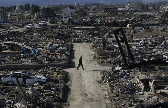 In this March 27, 2011 file photo, a man walks through the destroyed neighborhood below Weather Hill in Natori, Japan. Japan is marking the anniversary of the disaster Saturday, March 11, 2017 with somber ceremonies in Tokyo and in cities and towns in the northeast. Most of the towns devastated in the March 11, 2011 disasters have only partially rebuilt, and local authorities are struggling to finance construction. Meanwhile, despite an abundance of jobs thanks to the rebuilding, the population in most of the region is falling. (Photo by Wally Santana/AP Photo)
