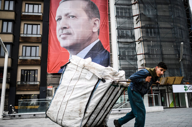 A man pulls a cart in front of a huge portrait of Turkish President Recep Tayyip Erdogan on Taksim Square in Istanbul on March 15, 2017. Turkey will hold its constitutional referendum on April 16, 2017. The controversial changes seek to replace the parliamentary system and move to a presidential system which would give President Recep Tayyip Erdogan executive authority. (Photo by Bulent Kilic/AFP Photo)