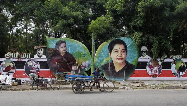 An Indian man pushes his cart past portraits of AIADMK leader Jayaram Jayalalitha on the day she is being sworn-in as the Chief Minister of Tamil Nadu state in Chennai, India, Saturday, May 23, 2015. An appeals court acquitted the powerful politician in southern India of corruption charges earlier this month, clearing the way for her to return to public office. (Photo by Arun Sankar K./AP Photo)