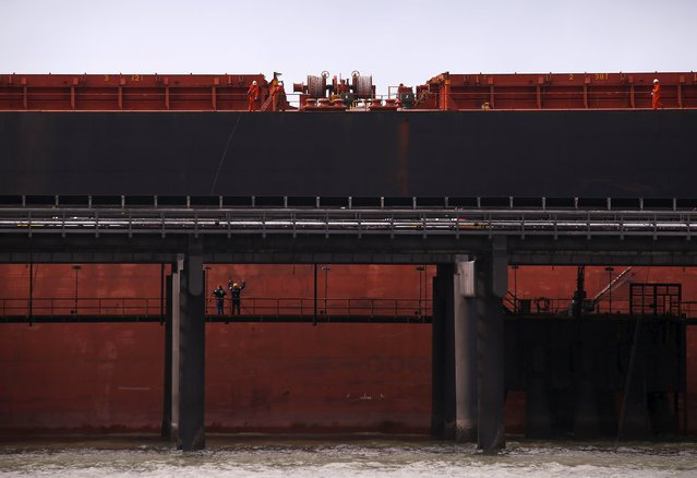 Port workers load a ship with coal at the RG Tanna Coal Terminal located at the town of Gladstone in Queensland, Australia, June 12, 2015. (Photo by David Gray/Reuters)