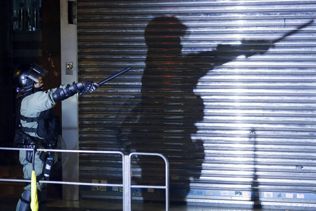 A riot policeman gestures as police disperse the residents and protesters at Sham Shui Po district in Hong Kong, Wednesday, August 7, 2019. Protesters surrounded a Hong Kong police station to demand the release of a university student arrested for apparently buying laser pointers, sparking the latest confrontation in the Chinese city. (Photo by Vincent Thian/AP Photo)