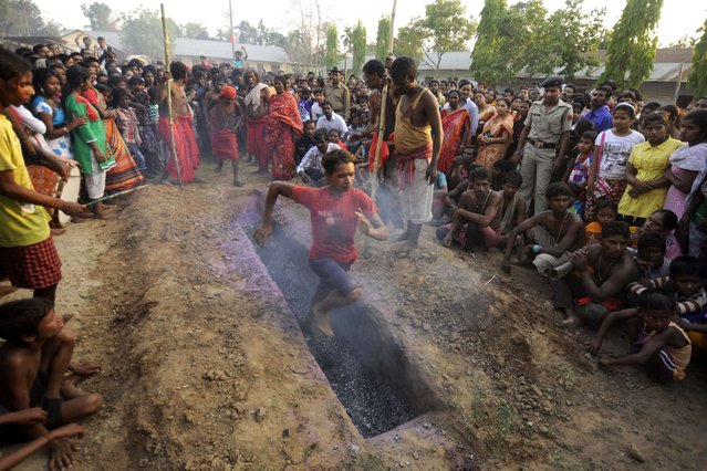 A Hindu devotee runs over smouldering charcoal during the ritual of Shiva Gajan at Pratapgarh village in Agartala, the capital of northeastern Indian state of Tripura, on April 14, 2014. Devotees believe that by enduring the pain, Shiva, the Hindu god of destruction, will grant their prayers. Thousands took part in the month-long festival which culminates with the worship of Shiva on the auspicious day of Chaitra Sankranti, the last day of the Bengali calendar year. (Photo by Arindam Dey/AFP Photo)