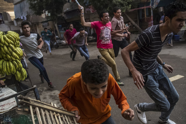 Supporters of the Muslim Brotherhood and bystanders run away from the Egyptian security forces during clashes following their protest on a street in Cairo's Matariya district, Egypt, Tuesday, June 30, 2015. Protesters were marching on a Cairo street Tuesday as authorities has declared the day a national holiday, two years after the mass protests that preceded the overthrow of President Mohammed Morsi. (Photo by Belal Darder/AP Photo)