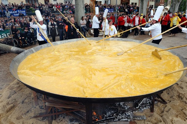 Toulouse's archbishop Mgr Robert Le Gall (2nd L) and members of the brotherhood of the Bessieres' giant Easter omelette prepare a giant omelette with thousands of eggs, on April 21, 2014 in Bessieres, southwestern France, as part of a traditional Easter celebration. (Photo by Remy Gabalda/AFP Photo)