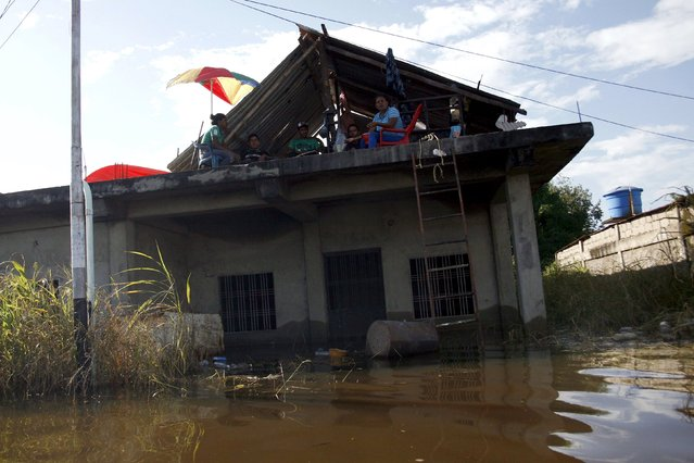 People sit on the roof of a house on a flooded street in Guasdualito, in the state of Apure, Venezuela, July 4, 2015. (Photo by Carlos Eduardo Ramirez/Reuters)