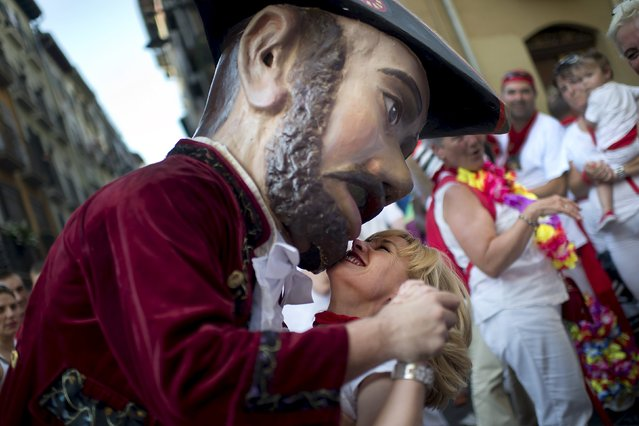 """A woman is embraced by a Kiliki during San Fermin festival's """"Comparsa de gigantes y cabezudos"""" (Parade of Giants and Big Heads) in Pamplona, northern Spain, July 6, 2015. (Photo by Vincent West/Reuters)"""