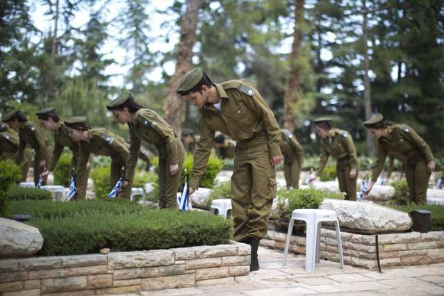 """Israeli soldiers decorating graves of fallen soldiers with small Israeli national flags, at the Mount Herzl military cemetery in Jerusalem, Israel, 08 May 2016. Israel is preparing to mark its """"Day of Remembrance for the Fallen Soldiers of Israel and Victims of Terrorism"""", which begins at sunset on 10 May 2016. (Photo by Abir Sultan/EPA)"""