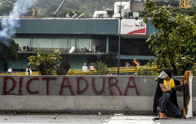 A demonstrator crouches during clashes with riot police within an opposition protest against Venezuelan President Nicolas Maduro, in Caracas on April 20, 2017. (Photo by Juan Barreto/AFP Photo)