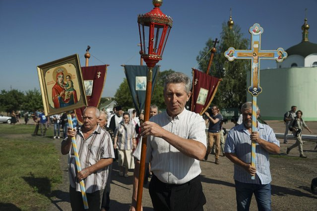 People carry an Orthodox cross and icons walk to attend a memorial service at the crash site of the Malaysia Airlines Flight 17, near the village of Hrabove, eastern Ukraine, Friday, July 17, 2015. (Photo by Mstyslav Chernov/AP Photo)