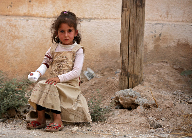 A Syrian girl sits on the side of a road after receiving treatment on October 20, 2019, in the Syrian border town of Tal Abyad which was seized by Turkey-backed forces last week. (Photo by Bakr Alkasem/AFP Photo)