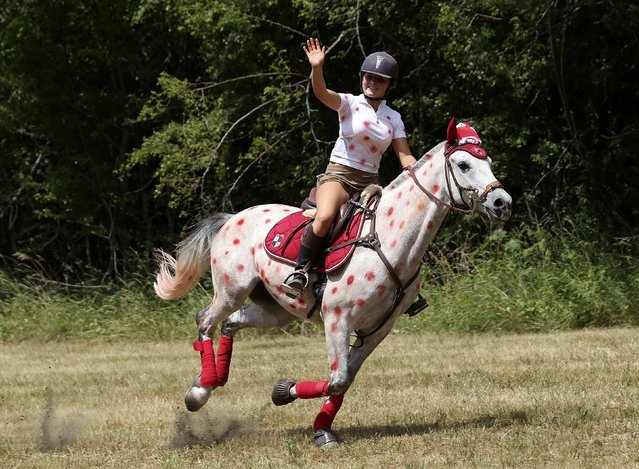 A girl ride a horse painted with red polka dots, in reference to the best climber jersey, during the 161-km (100 miles) 17th stage of the 102nd Tour de France cycling race from Digne-les-Bains to Pra Loup in the French Alps mountains, France, July 22, 2015. (Photo by Stefano Rellandini/Reuters)