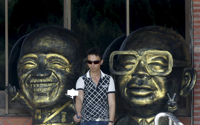 A man takes a selfie between figurines depicting Nationalist leader Chiang Kai-shek (L) and his son, Chiang Ching-kuo, in Taoyuan, nothern Taiwan, July 5, 2015. Dumped outside Chiang Kai-shek's mausoleum in Taiwan are nearly 200 unwanted statues of the Nationalist Party hero, a suggestion of the punishment his party faces in January elections for pushing the self-ruled island too close to political foe China. (Photo by Pichi Chuang/Reuters)