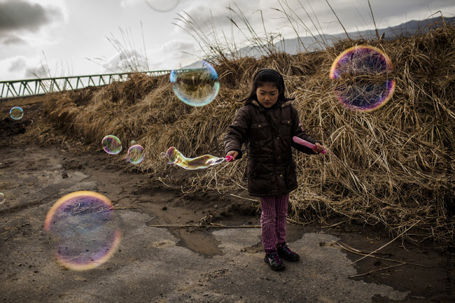 Hikari Oyama, 8,  plays with bubbles, after she and her grandmother payed their respects at the memorial to victims of the last year's tsunami at the Okawa Elementary School, where 74 children were killed and 4 are still missing, on March 11, 2012 near Ishinomaki, Japan