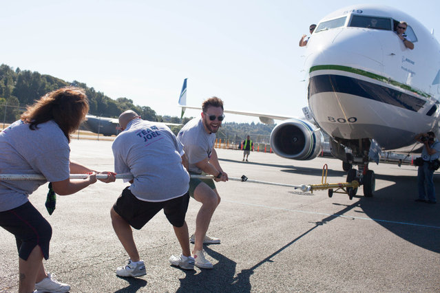 Joel McHale pulls the plane during the Alaska Airlines Plane Pull competition against Russell Wilson, benefiting Strong Against Cancer at The Museum of Flight in Seattle on Tuesday, July 28, 2015. Team Wilson pulled the 737 in 16.9 seconds, with Team Joel coming in at over a minute. (Photo by Matt Mills McKnight/AP Images for Alaska Airlines)