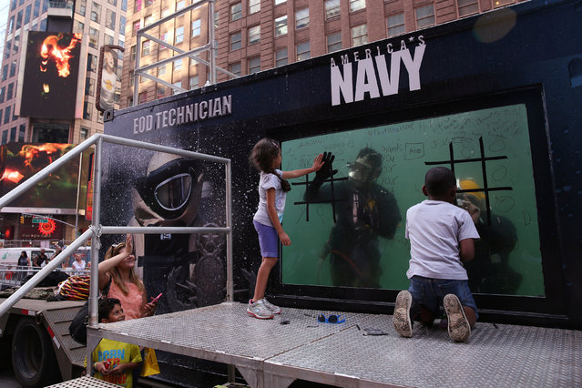 As a child plays tic-tac-toe, another presses her hand to the glass of a dive tank used by the U. S. Navy Mobile Diving and Salvage Unit for promotion during Fleet Week in Times Square in the Manhattan borough of New York, U.S., May 27, 2016. (Photo by Carlo Allegri/Reuters)