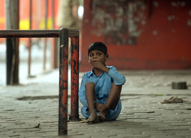 In this photograph taken on May 20, 2014 nine year old Indian boy Lakhan Kale is tied with a cloth rope around his ankle, to a bus-stop pole in Mumbai. (Photo by Punit Paranjpe/AFP Photo)
