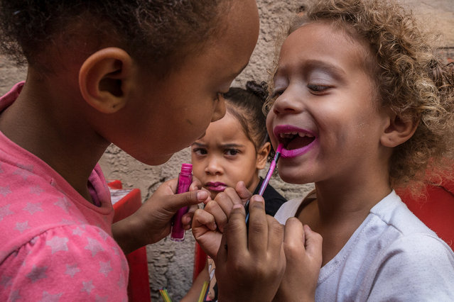 Girls have fun with lipstick and makeup. (Photo by Tariq Zaidi/The Guardian)
