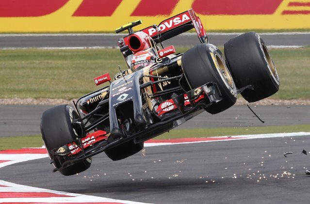 Lotus F1 team driver Pastor Maldonado goes off the track after colliding with Sauber driver Esteban Guitiererrez during the British Grand Prix at the Silverstone Race Circuit, central England, July 6, 2014. (Photo by Paul Hackett/Reuters)