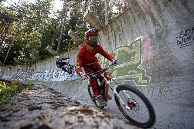Downhill bikers Kemal Mulic (R) and Kamer Kolar train on the disused bobsled track from the 1984 Sarajevo Winter Olympics on Trebevic mountain near Sarajevo, Bosnia and Herzegovina, August 8, 2015. (Photo by Dado Ruvic/Reuters)
