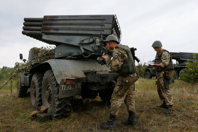 Ukrainian army reservists prepare a Grad multiple rocket launcher system during military exercise at a shooting range near the village of Goncharivske in Chernihiv region, Ukraine, June 22, 2016. (Photo by Valentyn Ogirenko/Reuters)