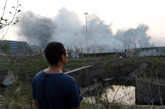 A man looks on as soke billows from the site of an explosion in Tianjin, northern China, on August 13, 2015. (Photo by Greg Baker/AFP Photo)