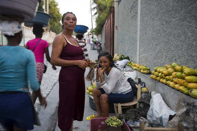 In this November 27, 2019 photo, Wadlande Pierre, right, talks on her mobile phone as she helps her mother, Vanlancia Julien, center, at their fruit and vegetable stand on a sidewalk in Delmas, a district of in Port-au-Prince, Haiti. Pierre, 23, said she temporarily moved in with her aunt in the southwest town of Les Cayes to escape the violent protests in Port-au-Prince. However, she had to move back to the capital because there was no gas, power or water in Les Cayes, and food was becoming scarce. (Photo by Dieu Nalio Chery/AP Photo)