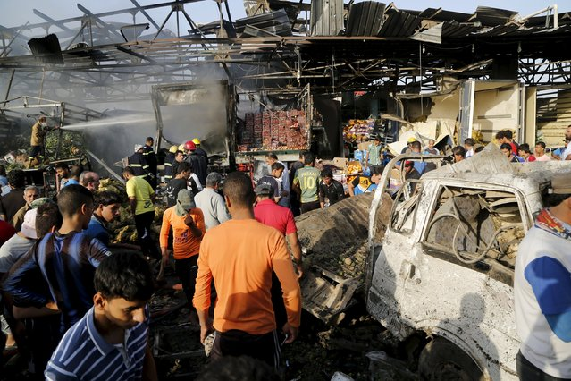 People gather at the site of a truck bomb attack at a crowded market in Baghdad August 13, 2015. (Photo by Wissm Al- Okili/Reuters)
