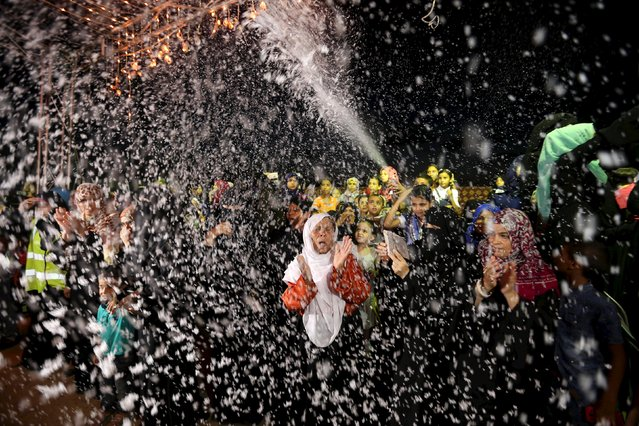Palestinians spray soap as they celebrate during a mass wedding for 53 couples in Khan Younis in the southern Gaza Strip August 13, 2015. The wedding was funded by the Islamic Society. (Photo by Ibraheem Abu Mustafa/Reuters)