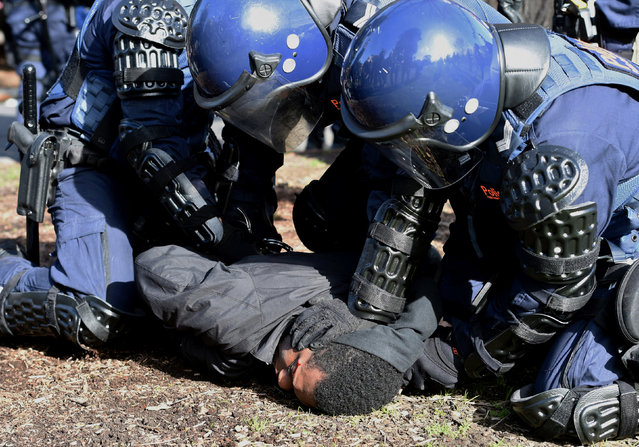 Riot police push a protester to the ground during clashes between anti-racism and anti-immigration activists during rallies located near Victoria's Parliament House in Melbourne, Australia, June 26, 2016. (Photo by Tracey Nearmy/Reuters/AAP)