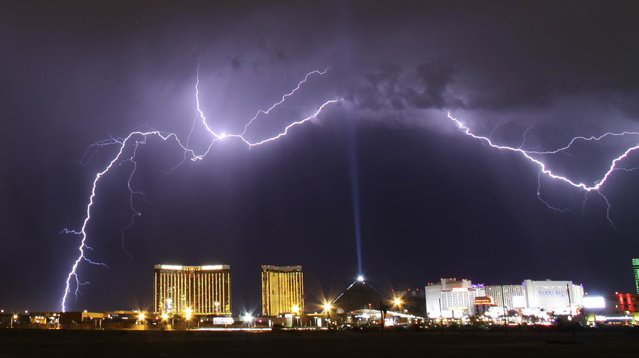 A monsoon lightning storm strikes over the Mandalay Bay Resorts and Casino and Luxor hotels in Las Vegas, Nevada late July 7, 2014. Monsoon storms are forecast for the the rest of the week in the Nevada and Arizona states. The Luxor Sky Beam can be seen shining into the sky from the top of the hotel's pyramid structure. (Photo by Gene Blevins/Reuters)