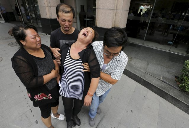 The mother (2nd R) of missing firefighter Xue Ning is helped by other family members as she cries outside the venue of a news conference after trying to demand for more information from government officials, following the explosions on Wednesday night at Binhai new district in Tianjin, China, August 15, 2015. (Photo by Jason Lee/Reuters)