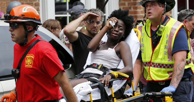 Rescue personnel help an injured woman after a car ran into a large group of protesters after an white nationalist rally in Charlottesville, Va., Saturday, August 12, 2017.  The nationalists were holding the rally to protest plans by the city of Charlottesville to remove a statue of Confederate Gen. Robert E. Lee. There were several hundred protesters marching in a long line when the car drove into a group of them. (Photo by Steve Helber/AP Photo)