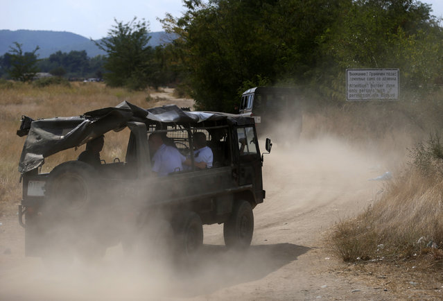 Police vehicles drive to the border between Greece and Macedonia, near the southern Macedonian town of Gevgelija, Thursday, August 20, 2015. (Photo by Darko Vojinovic/AP Photo)