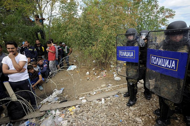 Macedonian police stand guard in front of migrants at the Greek-Macedonian border, August 21, 2015. (Photo by Alexandros Avramidis/Reuters)