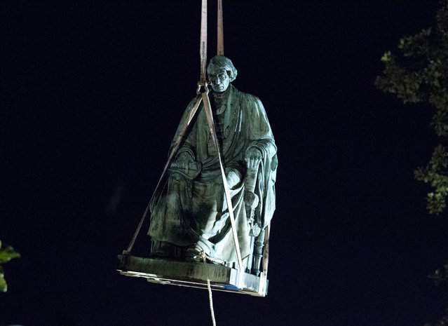 Workers use a crane to lift the monument dedicated to U.S. Supreme Court Chief Justice Roger Brooke Taney after it was was removed from outside Maryland State House, in Annapolis, Md., early Friday, August 18, 2017. Maryland workers hauled several monuments away, days after a white nationalist rally in Charlottesville, Virginia, turned deadly. (Photo by Jose Luis Magana/AP Photo)