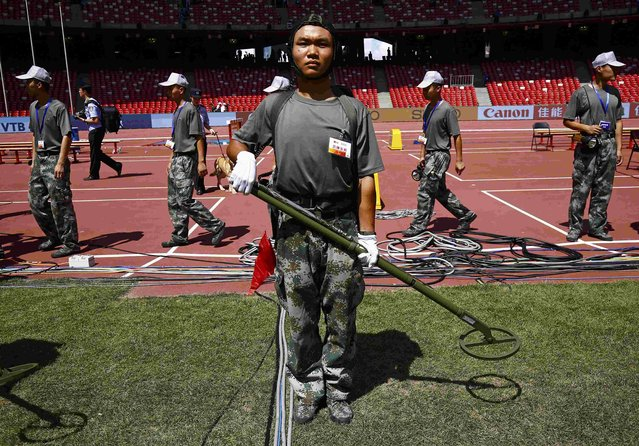 Security personnel sweep the infield with metal detectors after the first morning session and ahead of the opening ceremony during the 15th IAAF World Championships at the National Stadium in Beijing, China August 22, 2015. (Photo by Kai Pfaffenbach/Reuters)