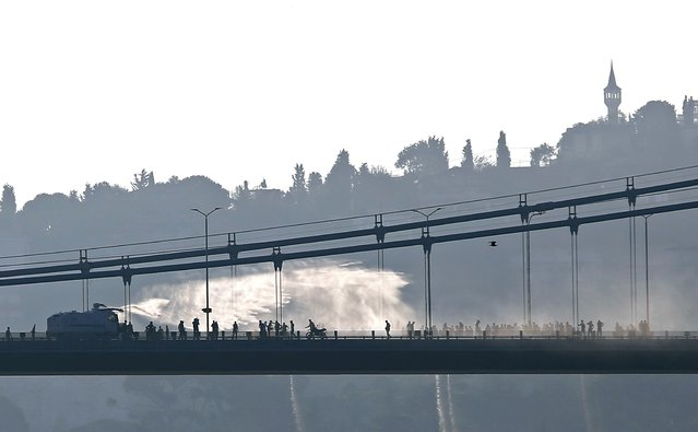 A police armored vehicle uses a water cannon to disperse anti-government forces on Bosphorus Bridge in Istanbul, Turkey, July 16, 2016. (Photo by Murad Sezer/Reuters)