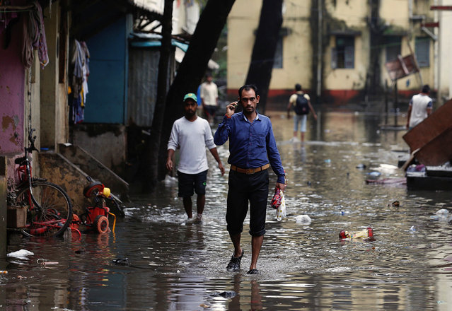 People walk through a partially flooded street at a residential area in Mumbai, August 30, 2017. (Photo by Danish Siddiqui/Reuters)