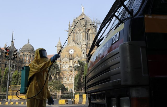A civic worker sanitizes the area outside Chhatrapati Shivaji terminus railway station during a lockdown to control the spread of the coronavirus in Mumbai, India, Thursday, April 2, 2020. India's 21-day lockdown has effectively kept 1.3 billion people at home for all but essential trips to places like markets or pharmacies. The steps were taken after a nationwide lockdown announced last week by Prime Minister Narendra Modi led to a mass exodus of migrant workers from cities to their villages, often on foot and without food and water, raising fears that the virus may have reached to the countryside, where health care facilities are limited. (Photo by Rajanish Kakade/AP Photo)