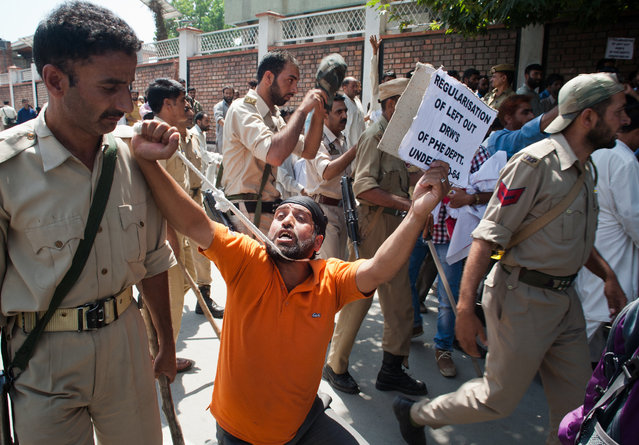 A daily wage employee holds a noose around his neck as Indian policemen try to disperse the crowd during a protest against the government on August  21, 2014 in Srinagar, the summer capital of Indian administered Kashmir, India. Indian police used water canons and batons to disperse dozens of daily wage employees protesting and demanding regulation of their services and a hike in monthly wages. (Photo by Yawar Nazir/Getty Images)