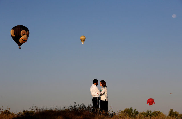 An Ultra-Orthodox Jewish couple stand together as hot air balloons fly overhead during a two-day international hot air balloon festival in Eshkol Park near the southern city of Netivot, Israel July 22, 2016. (Photo by Amir Cohen/Reuters)