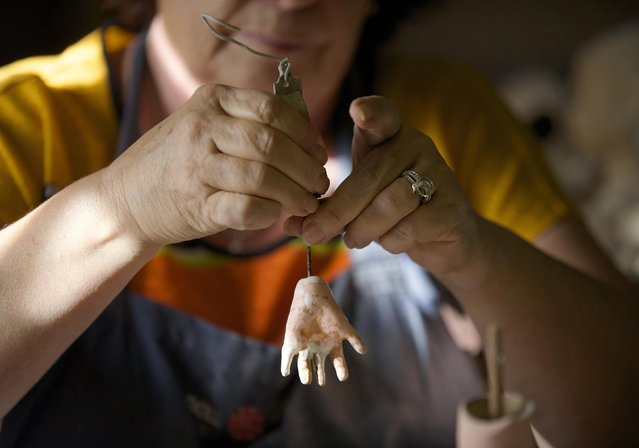 Gail Grainger, a 14-year veteran doll restorer, is pictured as she adds fingers to a damaged dolls hand in her workshop at Sydney's Doll Hospital, May 20, 2014. (Photo by Jason Reed/Reuters)