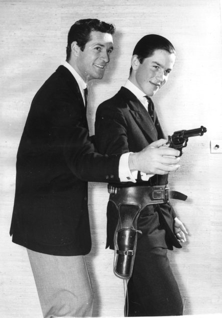 "Etonian Lord Rollo Fielding, son of the Earl of Denbigh, wears a holster during pistol practice with TV star Hugh O'Brien, who stars in the hit series ""Wyatt Earp"". 21st January 1959. (Photo by Keystone)"